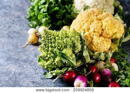Variety of fresh raw organic colorful cauliflower, cabbage romanesco and radish with bundle of coriander over dark texture background. Close up with space. Healthy eating concept