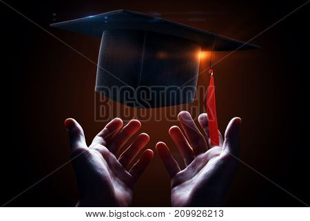 Hands holding glowing mortarboard on dark red background. Graduation concept