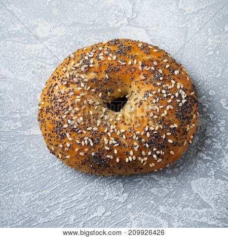 One bagel with poppy seeds and sesame seeds on a gray stone or concrete background. Selective focus. Top view. Copy space. Square image.