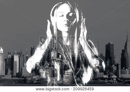 Attractive woman with closed eyes listening to music through headphones on city background. Relaxation hobby leisure concept. Double epxosure. Black and white image