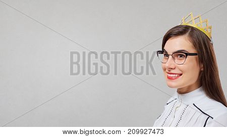 Business woman with a crown on her head on a gray background.