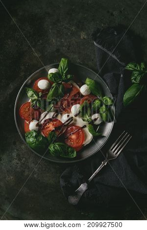 Italian caprese salad with sliced tomatoes, mozzarella cheese, basil in vintage metal plate with fork on textile napkin over dark metal background. Top view with space. Rustic style. Toned image