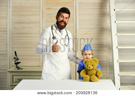 Vet And Assistant Hold Toy Pet And Show Thumbs Up