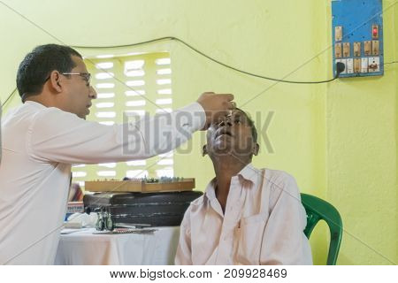 KOLKATA INDIA - MARCH 19 2017 : Male Doctor eye specialist checking eye sight of adult male sitting on a chair at a free public eye testing camp. Editorial stock image.