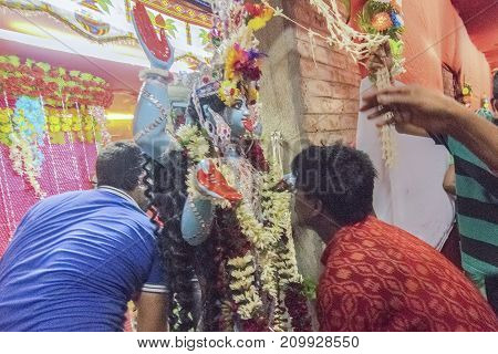 KOLKATA INDIA - JUNE 17 2017 - Hindu devotees worshipping Goddess Kali at night during Kali Puja Hindu festival of Deepavali or Diwali. Celebtated all over India. Shot under mixed light.
