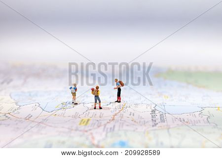 Miniature Group traveler with backpack standing on wold map for travel around the world. Travel Concept select focus