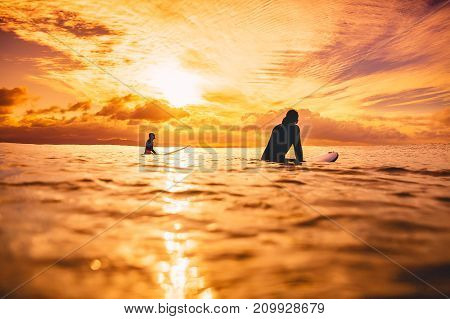 Surfers in ocean at sunset or sunrise. Couple of surfer and ocean