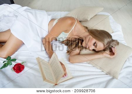 the girl fell asleep in bed with a book and a rose