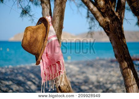 Straw hat, sunglasses towel on a background seascape with a pebble beach