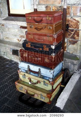 Vintage Suitcases On A Porter'S Trolley