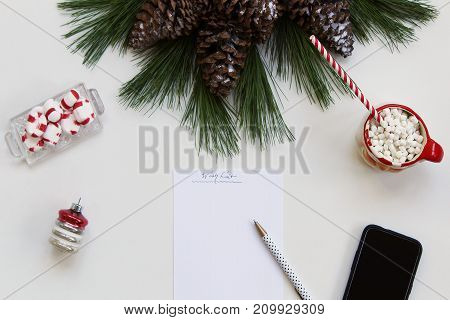 Christmas styled white desktop with nature greenery, candy, hot chocolate, wish list and cell phone. Copy space.