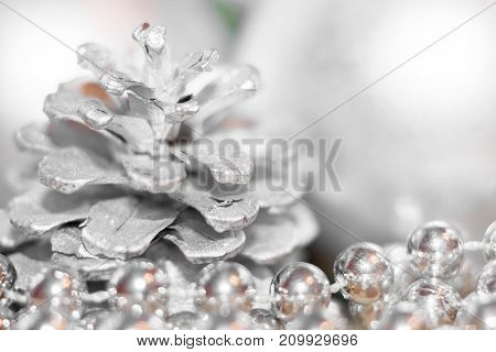 Abstract Christmas Background With Soft Focus. Silhouettes Of Silver Colored Pine Cone And Thread Wi