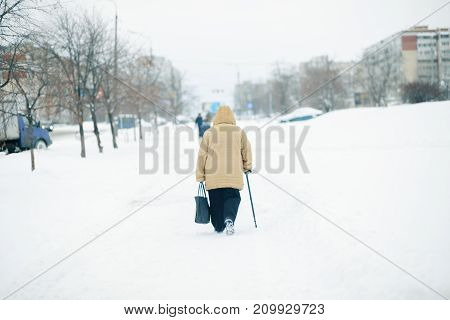 An elderly woman with cane is walking along a snow-covered pavement. Heavy snowfall in the city. Deep snow on a pedestrian road.