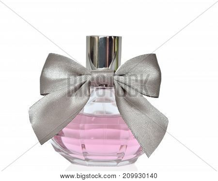 Women's perfume in beautiful round bottle with silver bow close up isolated on white background