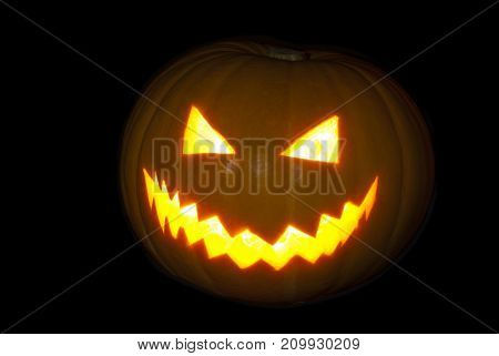 Classical pumpkin lantern brightly glowing from the inside on a black background