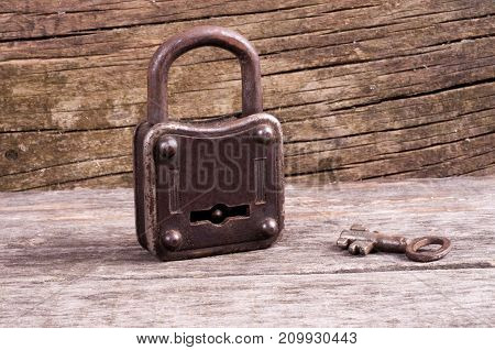 Grungy steel metal key and rusted lock on a old wooden boards background