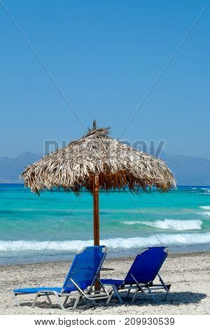 blue beach chairs with a beautiful view of the tropical, turquoise ocean under a straw umbrella on white sandy beach
