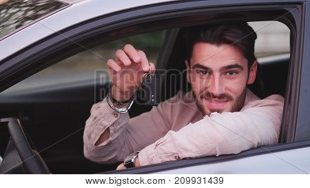 Handsome young man holding bunch of keys, looking in camera, sitting in his new car