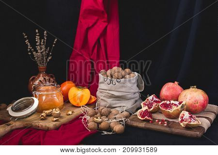 Autumn still life of honey bank, persimmon, nuts in a bag, pomegranate on a wooden board wrapped with jute tape dry lavender in a clay vase on a red-black background
