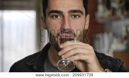 Seductive handsome young man sitting drinking toasting and celebrating with liquor in a shot glass as he gazes at the camera