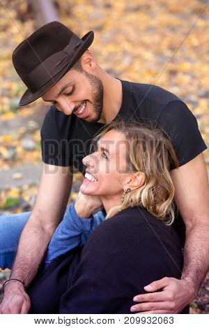 young beautiful couple sitting outside on train tracks and hugging each other