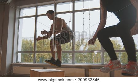 Young attractive girl and muscular man fitness instructor doing box jump exercise during a workout at the gym, horizontal