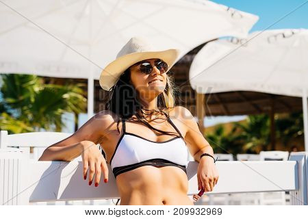Rich lifestyle woman relaxing enjoying luxury beach hotel,palms and umbrella around,expensive resort,summer vacations