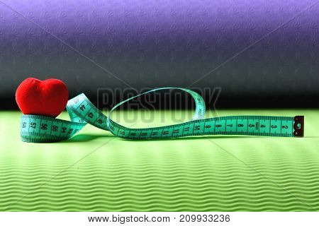 Heart Decoration And Flexible Ruler Lying On Yoga Mat