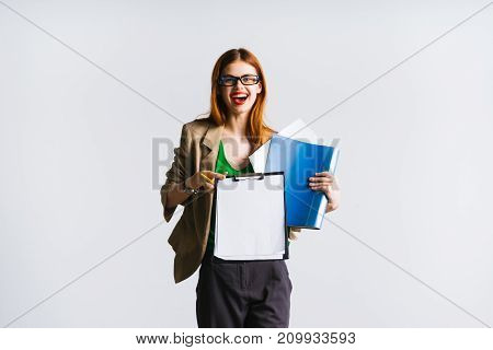 young modern successful girl in glasses and a strict suit holds important documents in her hands