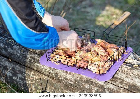 Pork in the marinade on the metal grill with onions and spices cooked for frying on coals outdoors