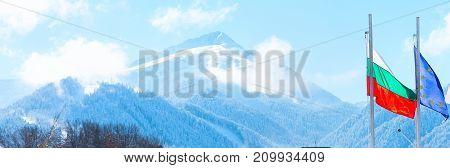 Winter ski resort background with white snow mountain peak, bulgarian flag and slopes in Bansko, Bulgaria