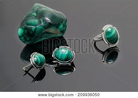 Closeup beauty silver earrings and ring with malachite on background of malachite stone piece on black acrylic desk.
