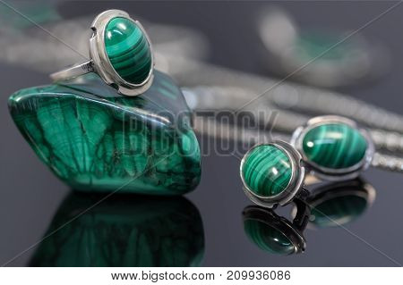Closeup vintage silver earrings and ring with malachite on top of malachite stone piece on background of silver chain on black acrylic desk.
