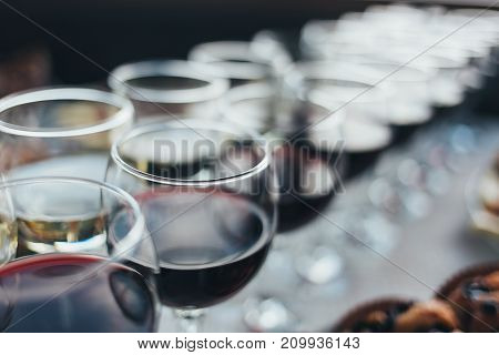 Many glasses of different wine in a row on bar