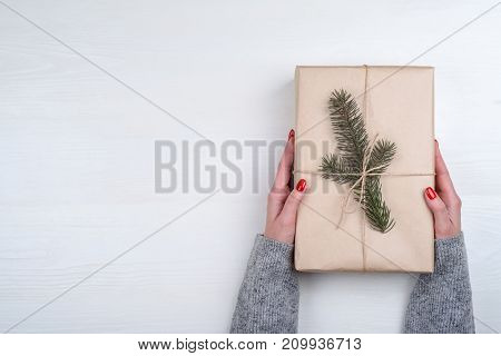 Woman with red manicure holding Christmas present wrapped in kraft paper on white wooden background free space. Close up of gift box in girl's hand. Christmas background. Flat lay top view