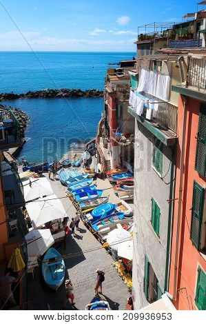 View from the top of the small marina of the village of Riomaggiore with moored boats and some tourists.