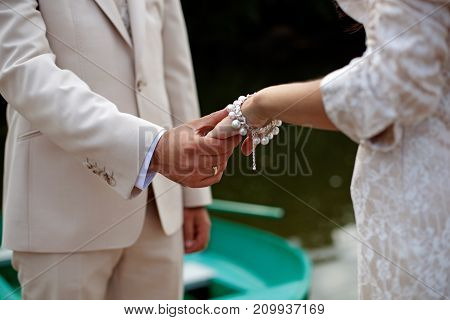 The Groom Gently Holds The Bride By The Hand