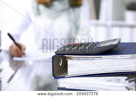 Calculator and binders with papers are waiting to be processed by businesswoman or secretary back in blur. Internal Audit and tax concept.