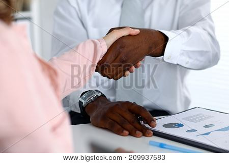 African american businessman shaking hands with female partner in office.