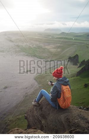 Girl in warm clothing, in red knitted hat and small orange backpack sits on the cliff and drinks coffee or tea on background of mountains in Iceland. Travel to the Iceland