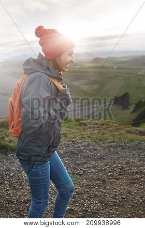 Girl stands on the cliff on background of sky and Reynisfjara beach in Iceland. Travel to the Iceland