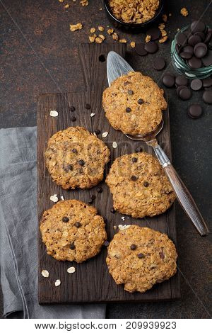 Stack of oatmeal cookies with chocolate and flakes on dark rusty concrete or stone background. Selective focus. Top view. Copy space.