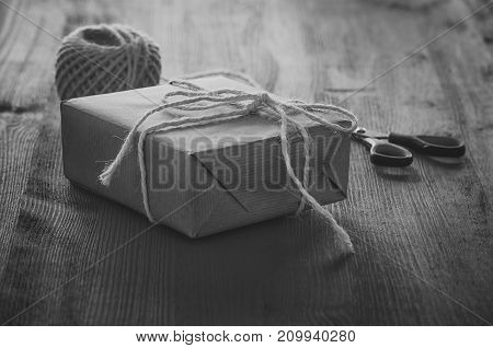 Black and white gift box - Monochrome image with a gift box wrapped in paper and tied with white string on a wooden table