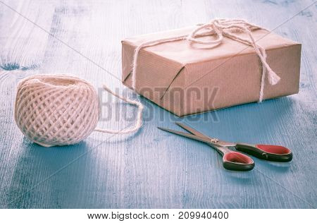 Self-made gift box  - Gift box homemade wrapped in classic brown paper ball of string and the scissors on a blue table
