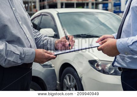 Insurance Agent examine Damaged Car and customer filing signature on Report Claim Form process after accident Traffic Accident and insurance concept.