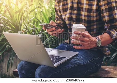Work and relax freelancer is working new project of business stragegy plan and using computer laptop and smart phone while sitting garden scenery outdoor background.