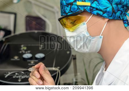 Male cosmetologist with medical mask on face and mesotherapy tool in hand.