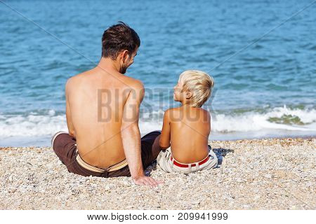 Beach son sandy father elementary age back view color