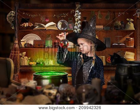 Room wizard. The little girl in the witch hat looking for the magic elixir in the retort. Many mystical items. The concept of magic Halloween