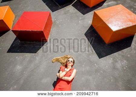 Woman in red dress lying on the ground with colorful cubes above the head. Thinking outside the box concept